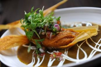 Alma Cocina's Pork Pibil Tamale is braised pork shoulder with bacon-corn masa, green chili sauce, crema and pico de gallo. Photo: AJC/Becky Stein
